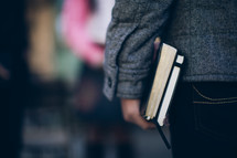 man holding a Bible and journal at his side as he heads to a Bible study