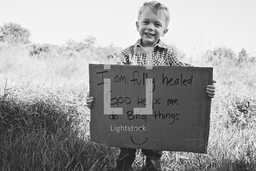 toddler boy holding a sign that reads I am fully healed. God helps me do BIG things.
