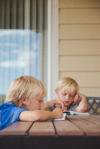 boys reading books outdoors at a table