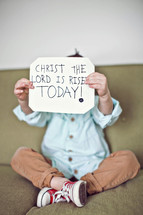 toddler holding a sign that reads Christ the Lord has risen today!