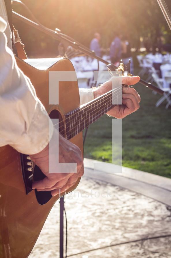 Hands strumming a guitar at an outdoor festival.