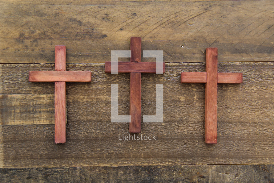 three wooden cross on a wood floor