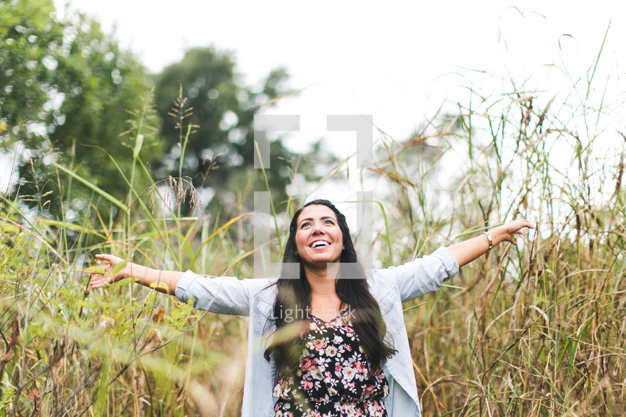 woman standing outdoors in tall grass with open arms