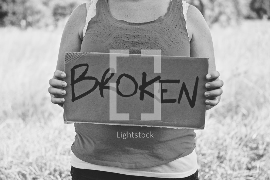 woman holding a sign with the words BROKEN