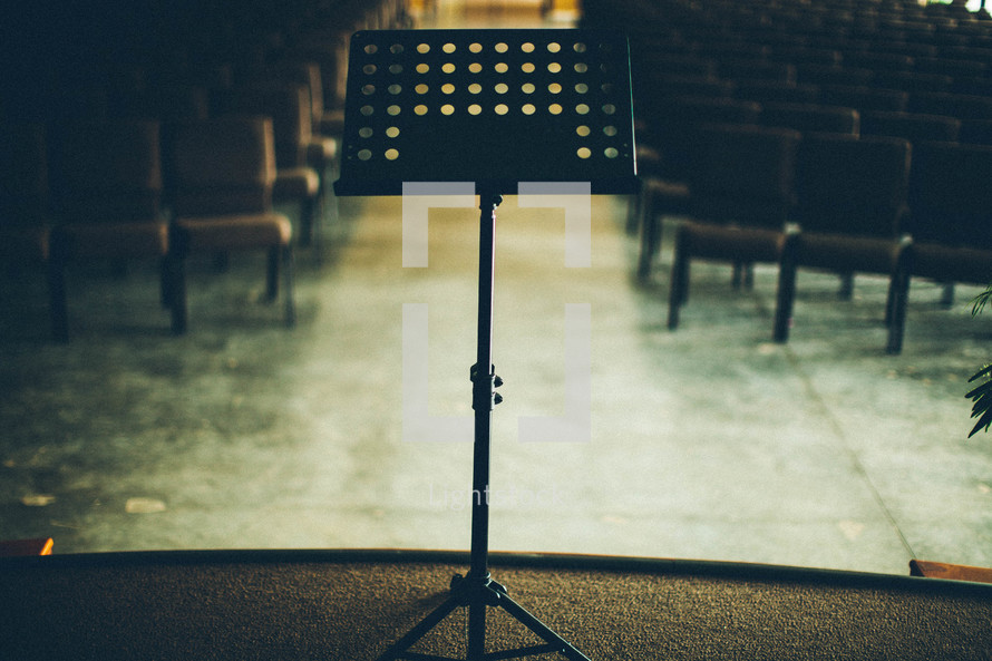 Music stand on stage in empty auditorium.