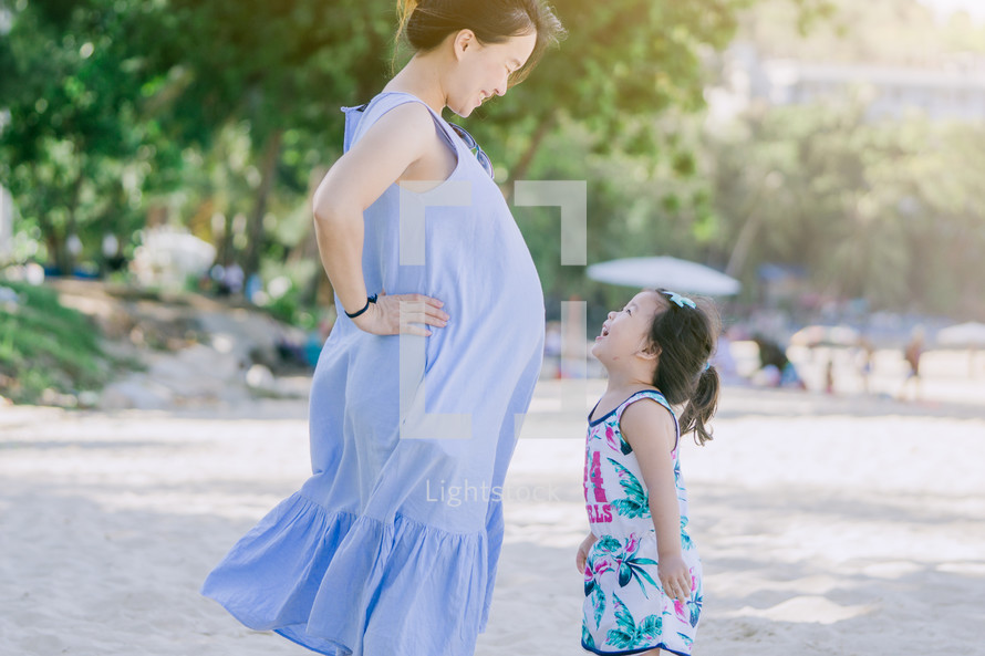pregnant mother and toddler daughter on a beach