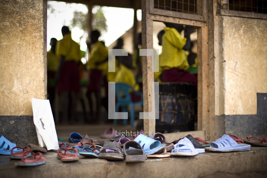 A collection of children's sandals sit outside a school room.