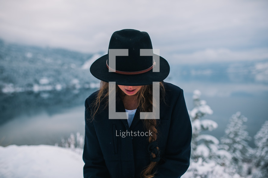 a woman in a hat standing on a snowy mountain top looking down