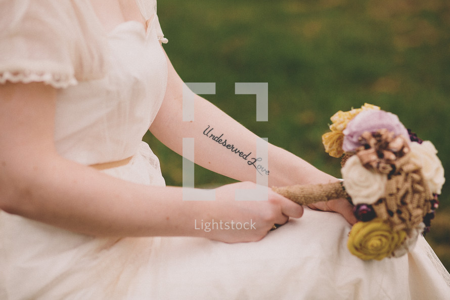 A bride with a tattoo holding a bouquet of flowers