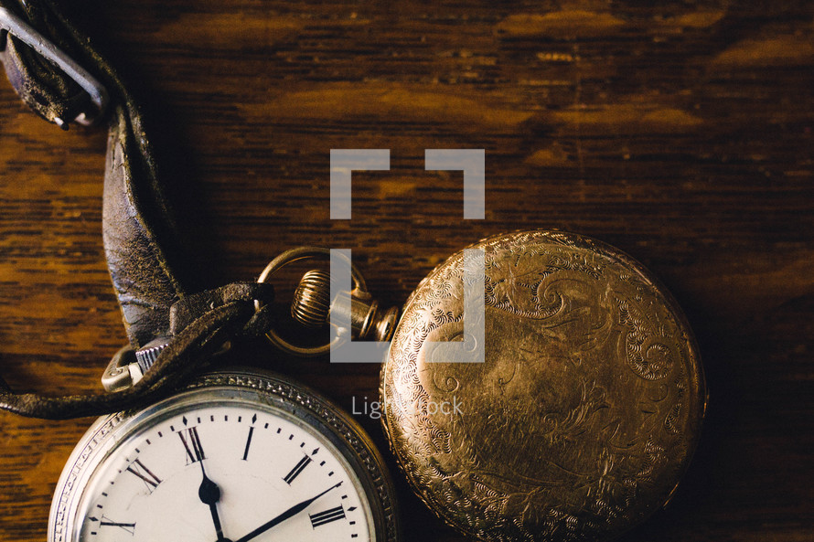 pocket watches on a wood table
