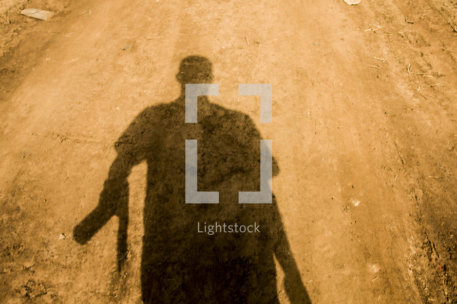 The shadow of a man walking down a dirt road