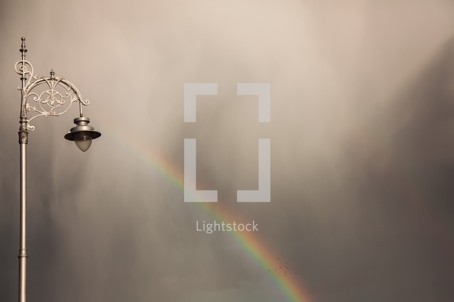 street light and rainbow against gray clouds