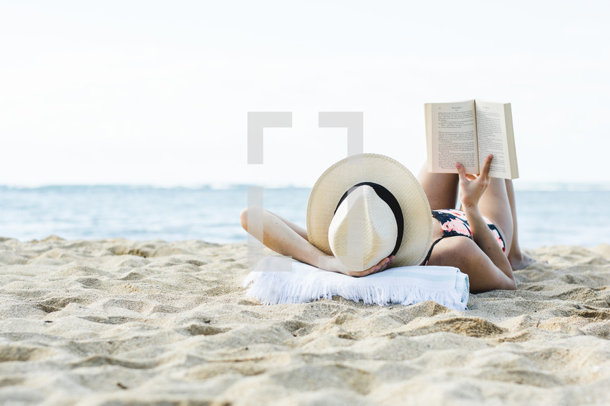 a woman reading a book on the beach in Hawaii