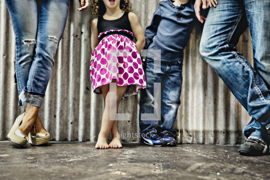 legs of a family in denim and a dress