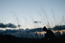 silhouette of a woman sitting outdoors at sunset