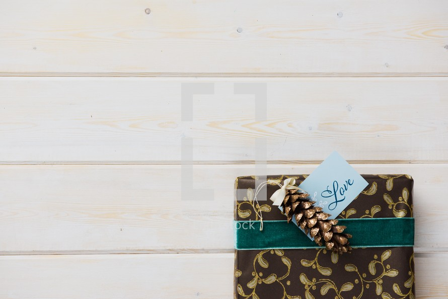 wrapped gift with pine cone on word boards