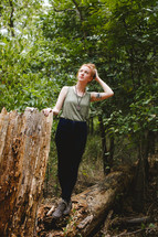 woman standing outdoors near a fallen tree
