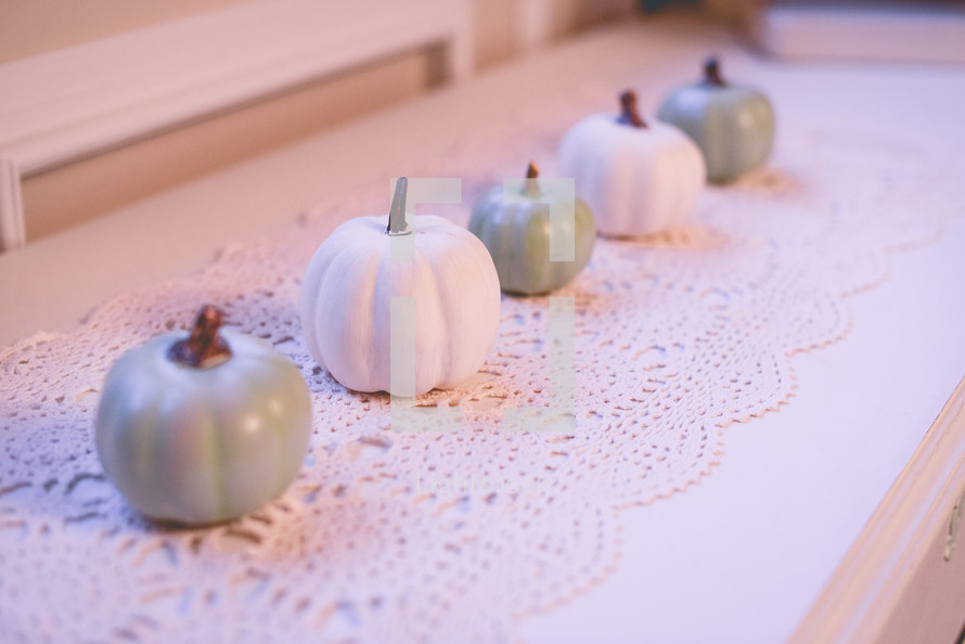 teal and white pumpkins on lace