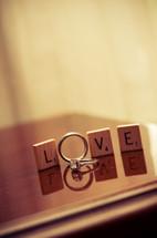 word LOVE in scrabble blocks and wedding rings