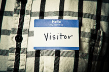 man wearing a name tag with the word visitor