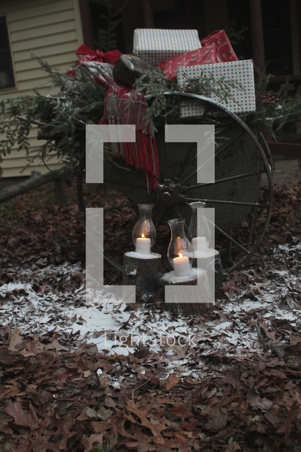 candles burning in glass lanterns in front of a carriage wagon full of presents dusted with snow