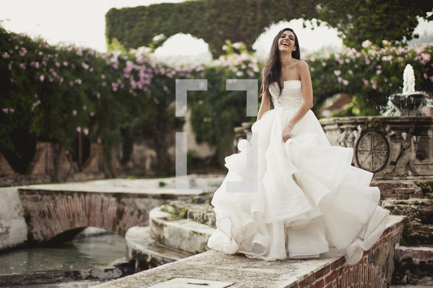 A smiling bride poses in her wedding dress near a fountain.