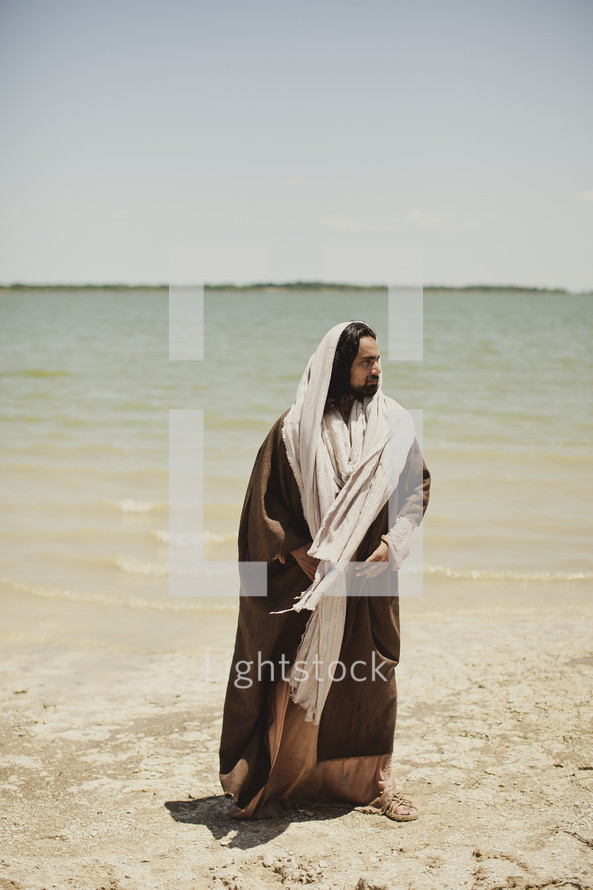 Jesus of Nazareth stands beside a lake.