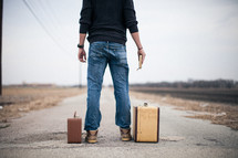 man standing next to suitcases holding a Bible looking down a long road and wondering where do I go from here