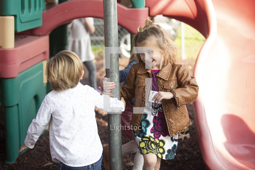 kids playing on a playground in church clothes