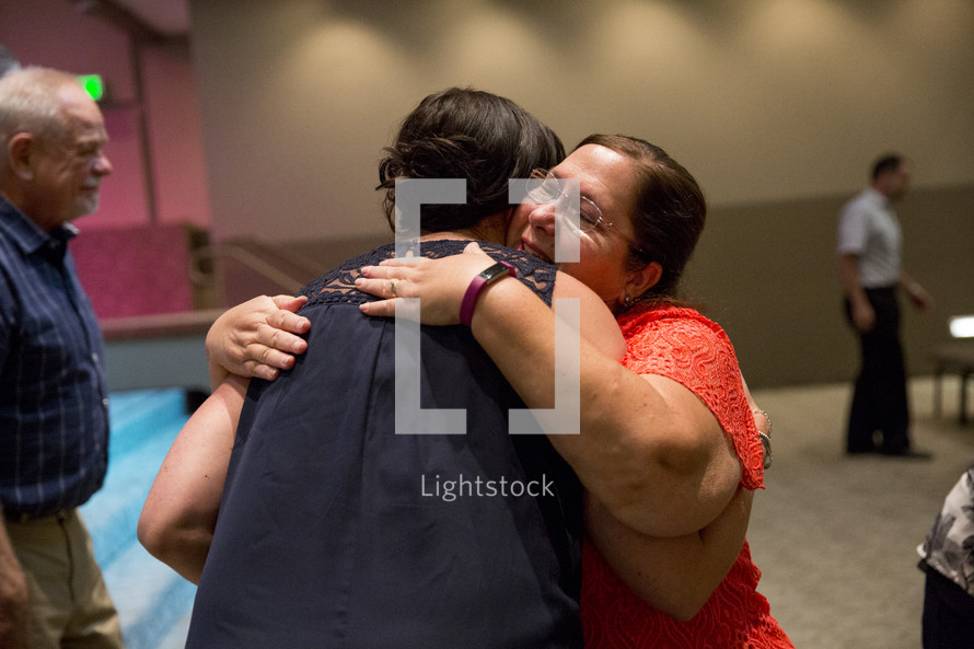 two women hugging during a worship service