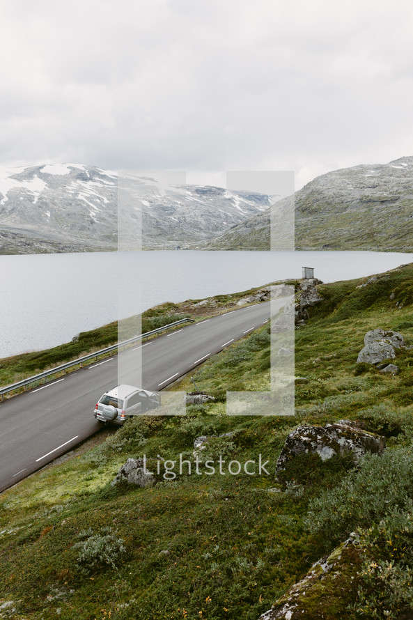 a car parked along the side of a curvy highway in Norway