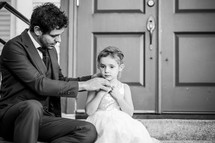 a father helping his daughter put on a necklace