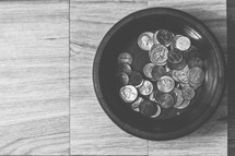 Coins in a wooden bowl.