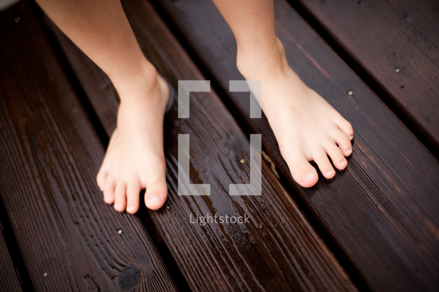 kids bare feet on a deck