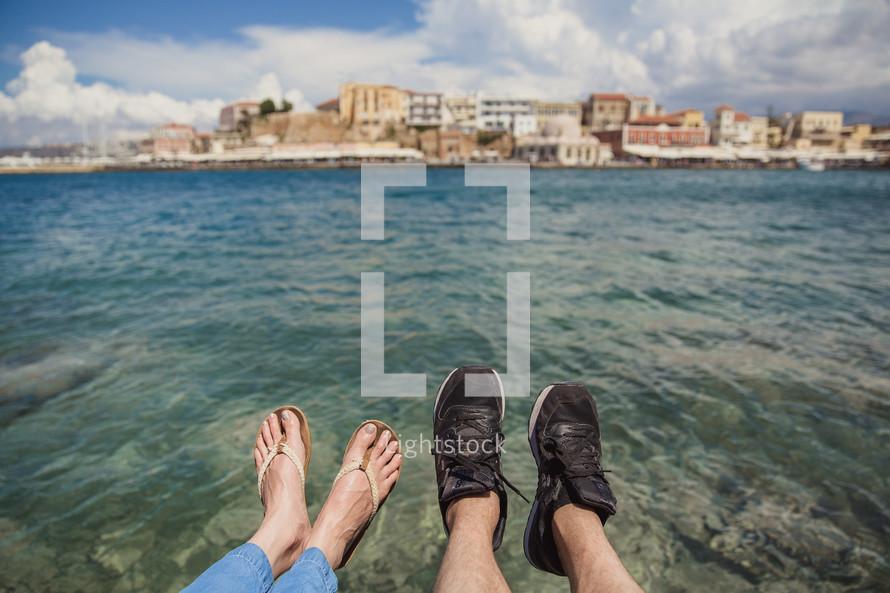 feet hanging over ocean water