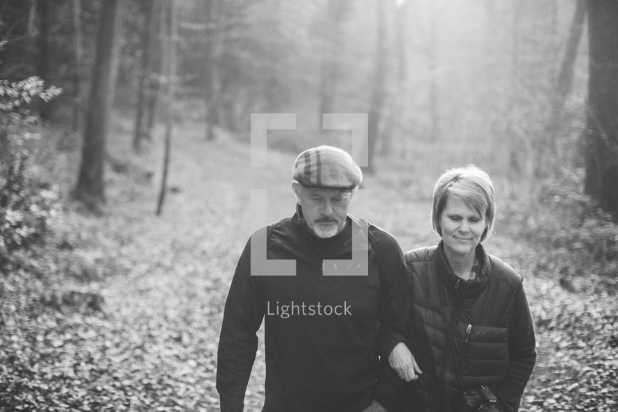 couple walking arm in arm on a trail