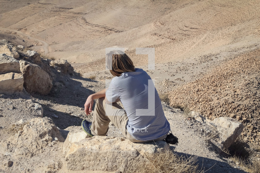 a person sitting in the desert in Jordan