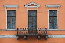 Side of a building with three windows and a balcony.