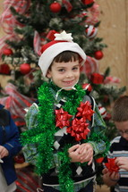 Boy covered in Christmas decorations.