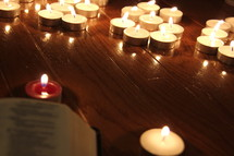 Bible in front of burning votive candles