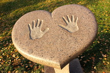 Handprints on a heart shaped table outdoors at a park.
