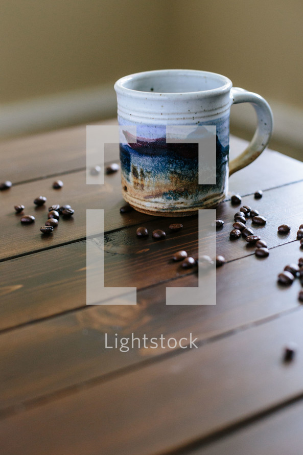 Coffee beans and a cup of coffee on a wooden table.