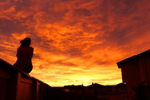 woman sitting outdoors under an orange sky at sunset