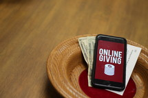 offering plate with a cellphone with an online giving app on the screen