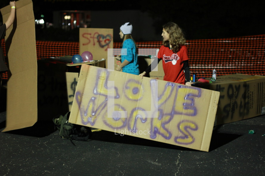 "Teens holding cardboard ""love"" signs."