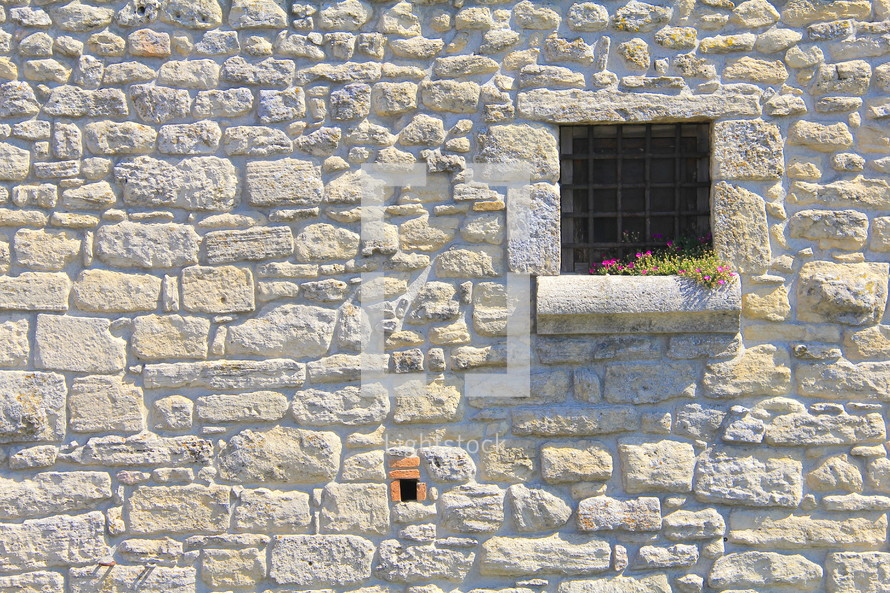 barred window on a castle with flowers growing along the window sill