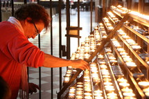 Lady saying a prayer and lighting a votive or prayer candle in a Catholic Cathedral.