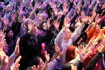 Worshippers with arms raised at a church service. People making a decision for Christ at an evangelistic outreach.