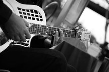 man playing a steel guitar slide capo