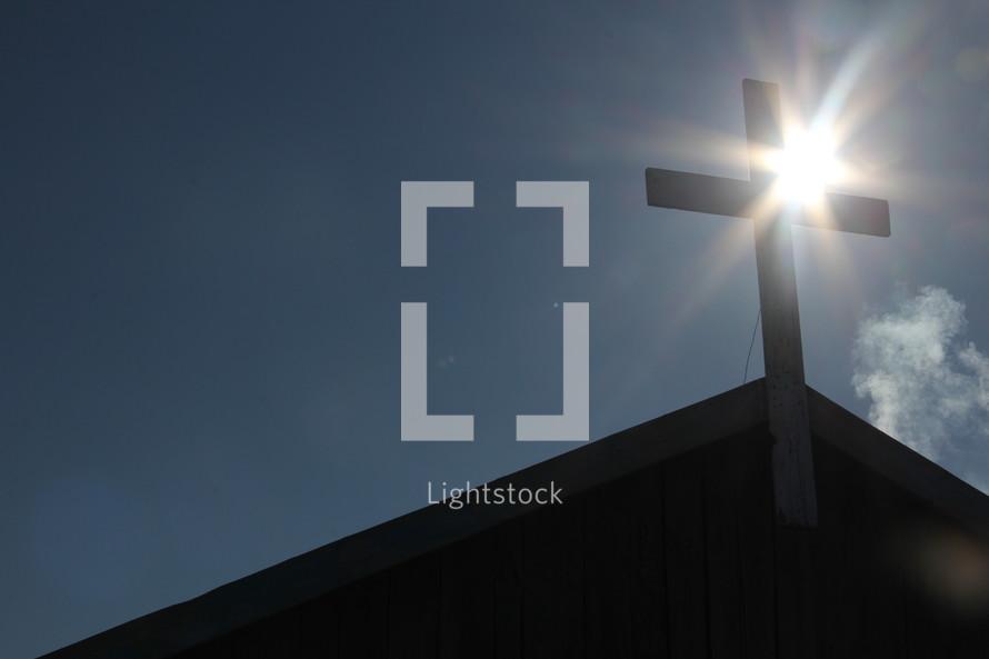 Mongolian church cross with winter sun radiating behind